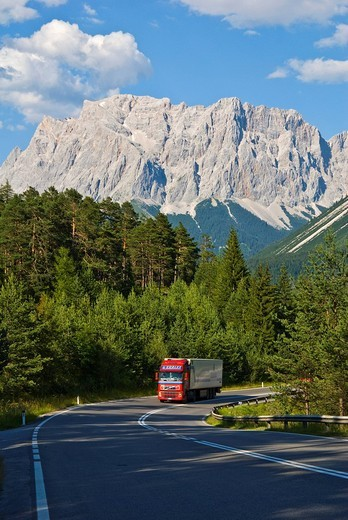 Stock Photo: 1848-30426 Red truck climbing the Fernpass mountain pass road, Mt. Zugspitze at back, Wetterstein Range, Tyrol, Austria