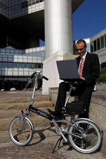 Stock Photo: 1848-30896 Businessman on his way to work on a folding bike, Hypobank building, Bogenhausen, Munich, Bavaria, Germany, Europe