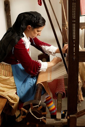 Woman weaving a carpet on an historical loom, public demonstration of handicraft, Serrastretta, Calabria, Italy : Stock Photo