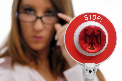 Woman holding a red police signalling disk with the federal eagle : Stock Photo