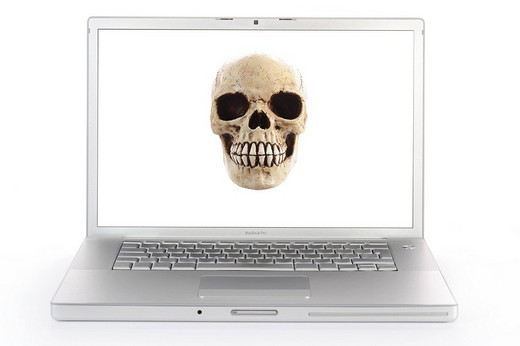 Skull on a computer screen, symbolic image for a virus Alert : Stock Photo