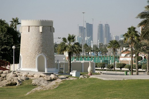 Qatar, Doha, historic stronghold tower in a park, in the background high_rise buildings, construction site : Stock Photo