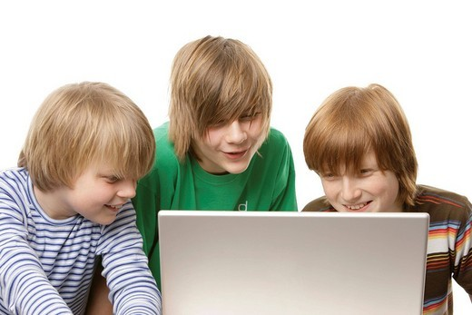 Three boys sitting in front of a laptop, 10, 12 and 13 years old : Stock Photo