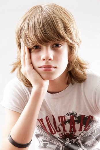 12 year_old boy looking into the camera, wresting his head in his hand : Stock Photo