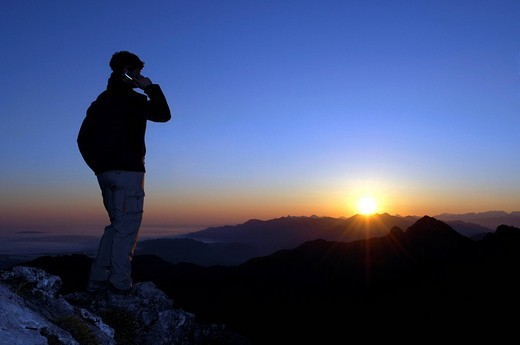 Man with mobile phone at sunrise on a mountain top, Breitenstein Mountain, Bavarian foothills, Wendelstein Group, Upper Bavaria, Bavaria, Germany : Stock Photo