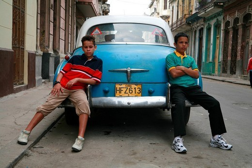 Stock Photo: 1848-38250 Two boys casually leaning against a vintage car with a couple making out in the back seat, Havana, Cuba, Caribbean, Americas