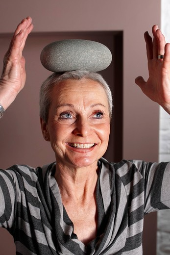 Women, Best Ager, balancing a stone on her head : Stock Photo