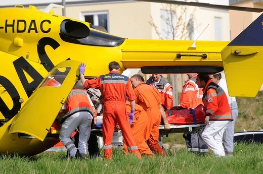 Stock Photo: 1848-401184 ADAC rescue helicopter Christoph, landing in a field, the patient is brought into the rescue helicopter, Baltmannsweiler, Baden_Wuerttemberg, Germany, Europe