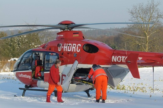 Rescue helicopter Christoph 41, identifier D_HDRC, landing on a snow_covered meadow, in front a Porsche Cayenne ambulance of the fire departement, Stuttgart, Baden_Wuerttemberg, Germany, Europe : Stock Photo