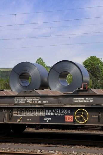 Stock Photo: 1848-403519 Strip steel rolls on a heavy load train, above overhead lines, transportation of goods by rail