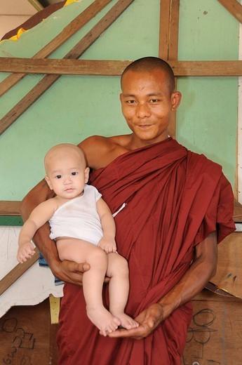 Buddhist monk with an albino baby near the Shwedagon Pagoda, Yangon, Myanmar, Burma, Southeast Asia : Stock Photo