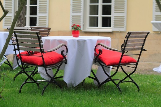 Stock Photo: 1848-405460 Table covered with white tablecloth standing on grass in a garden restaurant, floral decoration and red cushions, at back, historic facade