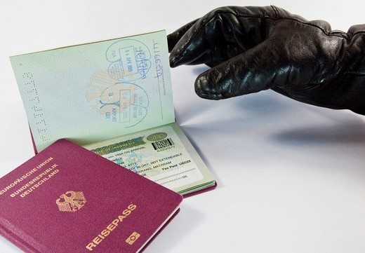Gloved thief trying to steal a passport : Stock Photo