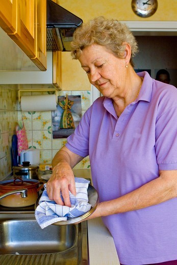Pensioner drying dishes : Stock Photo