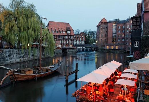Historical salt port on the Ilmenau river, evening mood, illuminated restaurant terraces, Lueneburg, Lower Saxony, Germany, Europe : Stock Photo