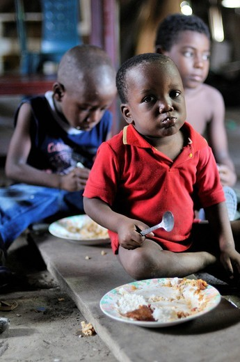 Stock Photo: 1848-407574 Afro_Colombian children eating a simple meal on the floor of a shabby wooden hut, Bajamar slum, Buenaventura, Valle del Cauca, Colombia, South America