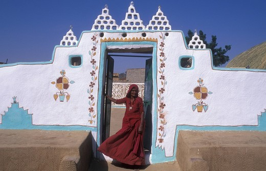 Traditionally painted facade of a house, a woman wearing a sari standing at the entrance, Thar Desert, Rajasthan, India, Asia : Stock Photo