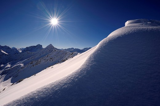 Stock Photo: 1848-408125 Snow cornice with a star_shaped sun in front of a mountain panorama, Rietzler, Kleinwalsertal, Vorarlberg, Austria, Europe