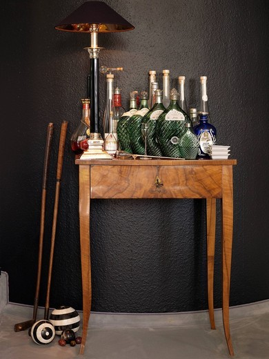 Antique side table with lamp, old golf clubs and fine bottles : Stock Photo