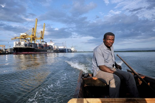 Simple fisherman in his boat, in the back cargo ships in the seaport of Buenaventura on Colombia´s Pacific coast, Buenaventura, Valle del Cauca, Colombia, South America : Stock Photo