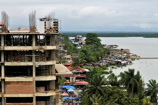 Land conflict, modern high_rises replace the traditional quarters on the mangrove banks of the Rio Anchicaya river, Buenaventura, Valle del Cauca, Colombia, South America : Stock Photo