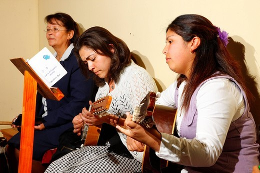 Women playing guitar during church service, mining town of Lota, Chile, South America : Stock Photo