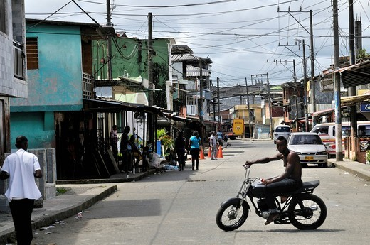 Street and a young darkskinned man on a motorcycle in the Bajamar slum, Buenaventura, Valle del Cauca, Colombia, South America : Stock Photo