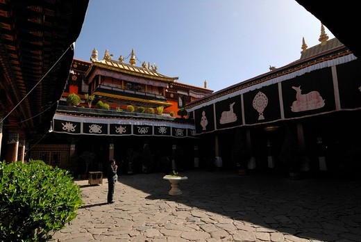 View from the courtyard towards the gilded roofs of the Jokhang Temple with a man praying, Lhasa, Tibet, China, Asia : Stock Photo