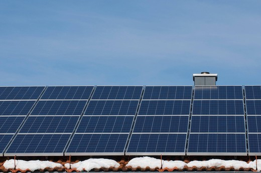 Solar panels on the roof of a house with patches of snow, renewable energy : Stock Photo