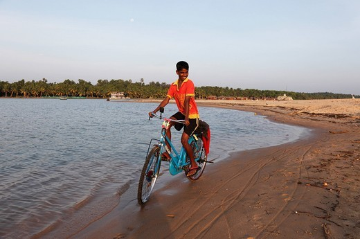 Stock Photo: 1848-412666 Proud boy riding a bike along the Poovar River, backwater, in front of the Hotel Isola di Cocco Resort, Puvar, Kerala, South India, India, Asia