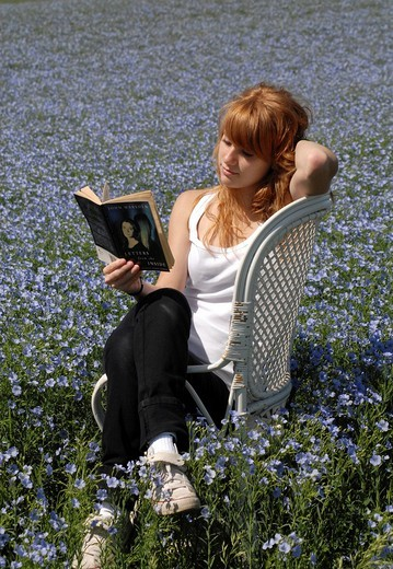 Reading girl sitting in a chair in a field of linen : Stock Photo
