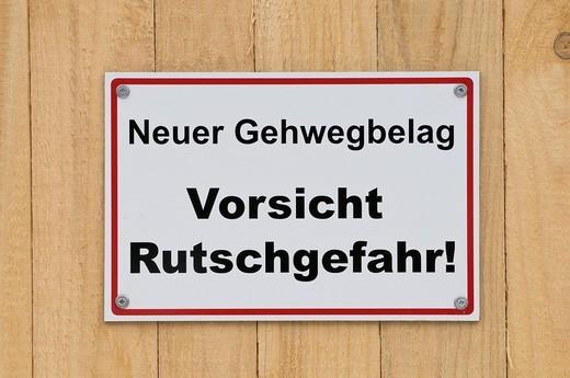 Stock Photo: 1848-413168 Sign on wooden board fence, Neuer Gehwegbelag Vorsicht Rutschgefahr, new walkway surface, caution slip hazard!