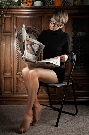 Young woman in pantyhose and glasses reading a newspaper : Stock Photo