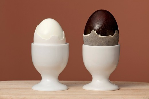 1 hen´s egg and 1 fermented duck egg, also known as century egg, preserved egg, hundred_year egg, thousand_year egg, or thousand_year_old egg, egg cups : Stock Photo
