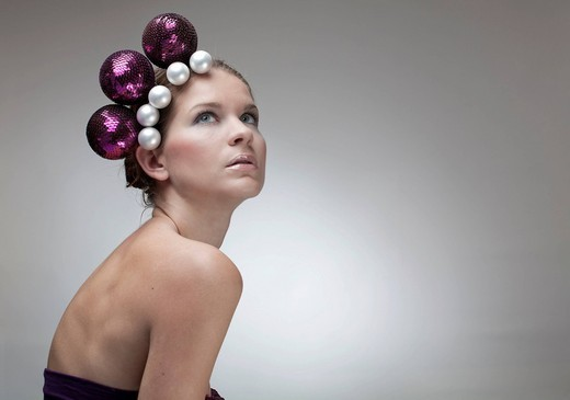 Portrait of a young woman, Christmas balls as hair ornaments, purple, sequined top : Stock Photo