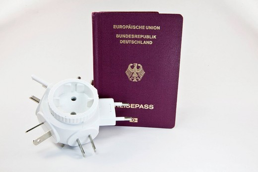 Preparations for a business trip, passport and power plug travel adapter : Stock Photo