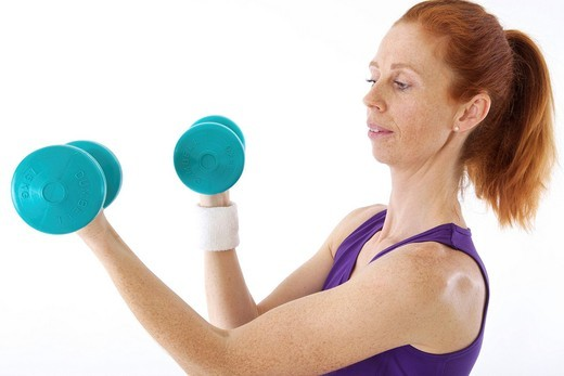 Stock Photo: 1848-416270 Woman exercising with dumb_bells