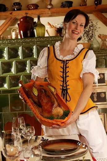 Young woman presenting roast goose, rustic : Stock Photo