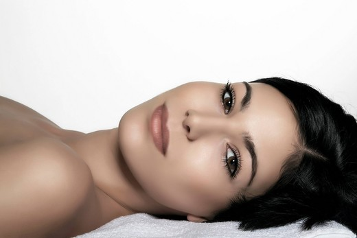 Stock Photo: 1848-417094 Young dark_haired woman lying on her back, direct look, beauty