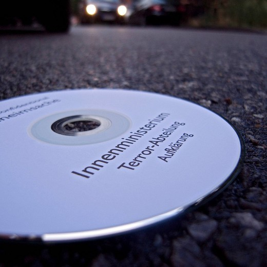 CD labeled with Innenministerium, Ministry of the Interior and Terrorabteilung, Department of Terror, lying on the road : Stock Photo