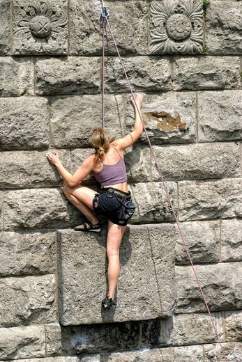 Stock Photo: 1848-417993 Woman climbing a wall next to the Hohenzollernbruecke Bridge in Cologne, North Rhine_Westphalia, Germany, Europe