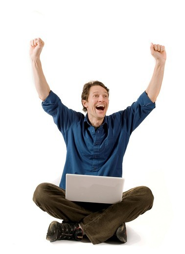 Cheering man with laptop sitting cross_legged : Stock Photo