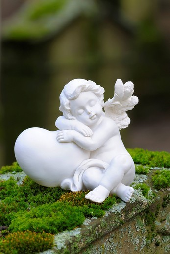 Angel figurine made of clay on mossy stones : Stock Photo