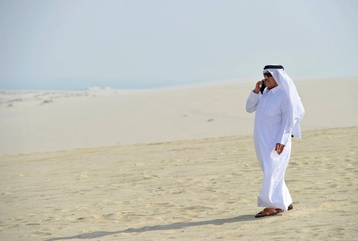 Qatari on a cell phone, in traditional clothing with gutra, Emirate of Qatar, Persian Gulf, Middle East, Asia : Stock Photo