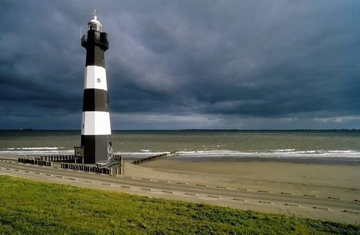 Lighthouse on the Walcheren peninsula, dark clouds over the sea, stormy atmosphere, Zeeland, Netherlands, Europe : Stock Photo