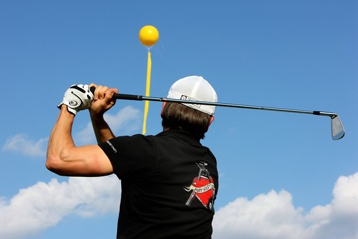 Stock Photo: 1848-425682 Member of the Pottgolf Golf Club at a game of golf, RedGolf golf course on the former Zeche Jacobi colliery, in the back a yellow balloon as part of the Schachtzeichen art project of the Kulturhaupstadt_Jahr Ruhr2010 Capital of Culture_year, 311 yellow ba