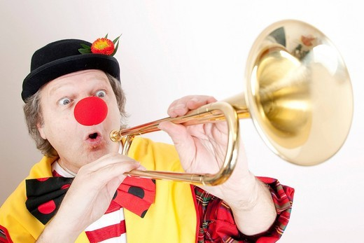 Clown with a fanfare horn, natural trumpet or clarion : Stock Photo