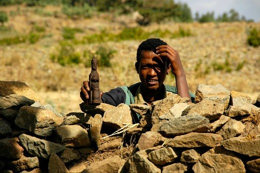 Boy standing behind a stone wall holding a holy figurine in his hand, Axum, Ethiopia, Africa : Stock Photo
