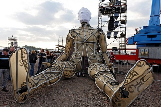 Giant figure sitting on the floor, Global Rheingold, open_air theater by La Fura dels Baus, Duisburg_Ruhrort, Ruhrgebiet area, North Rhine_Westphalia, Germany, Europe : Stock Photo