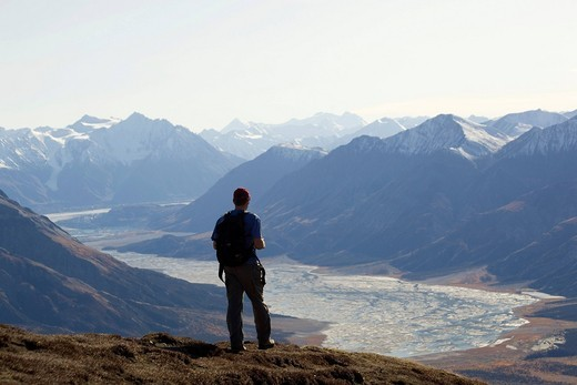Hiker, man hiking, enjoying panorama, view from Sheep Mountain into Slim´s River Valley, Kaskawulsh Glacier, St. Elias Mountains, Kluane National Park and Reserve, Yukon Territory, Canada : Stock Photo
